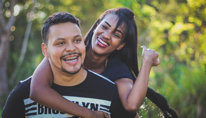 Dark-haired woman embracing a man from the back as they both smile while wearing braces outside in front of trees