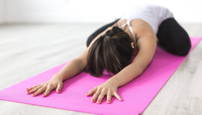 Brunette woman wears exercise clothes and lies in Child's Pose on a pink yoga mat