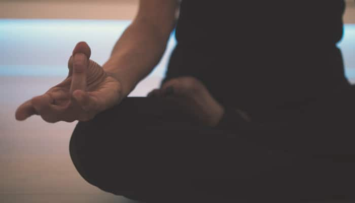 Closeup of a woman sitting cross-legged with her fingers gently pinched together in zen pose of meditation