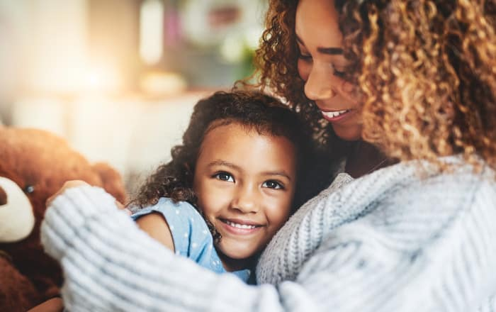 Curly-haired mother in a light gray sweater embraces her daughter who still has baby teeth while sitting on a couch