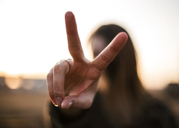 Closeup of a woman holding up 2 fingers to represent biannual dental visits
